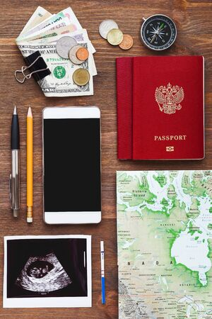 Travel while being pregnant background. Different things you need for journey - smartphone, passport, map, money. Ultrasound photo of baby and positive pregnancy test. 版權商用圖片