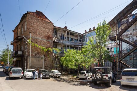 TBILISI, GEORGIA - May 01, 2017. Old narrow street in Tbilisi, Georgia. Old building with retro wooden balconies, wires. Editorial