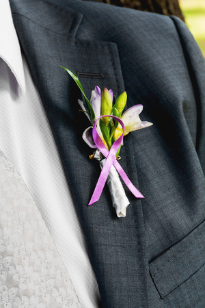 Boutonniere with Freesia flowers and leaves. Traditional groom accessory at the wedding.