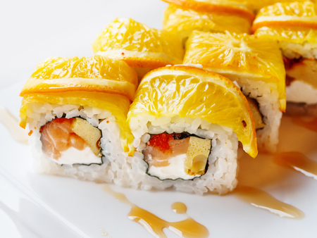 Rolls with rice, seaweed nori, salmon, cream cheese, chicken egg, caviar masago, orange. Marinated ginger and wasabi sauce. Asian cuisine, traditional dish - sushi. Stock Photo