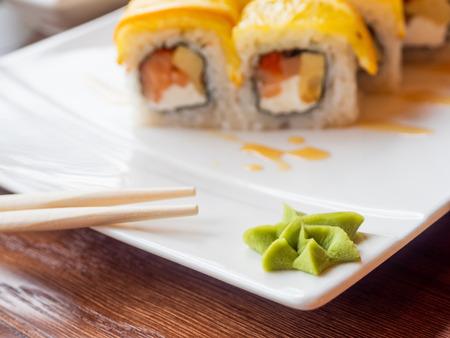 Wasabi sauce and rolls with rice, seaweed nori, salmon, cream cheese, chicken egg, caviar masago, orange. Wasabi sauce. Asian cuisine, traditional dish - sushi.