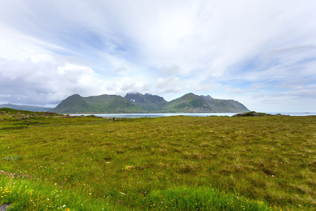 Beautiful scandinavian landscape with meadows, mountains and village. Lofoten islands, Norway.