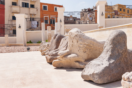 Houses outside the fence and Sphinx statues in the Serapeum of Alexandria. Ancient architectural landmark in Egypt. Фото со стока