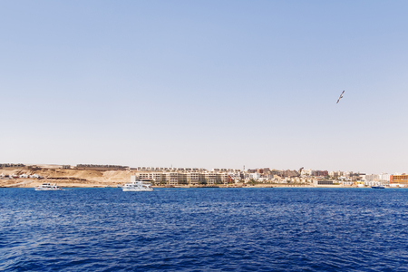 Hurghada coastline with hotel and resort buildings. View on seascape from boat. Red sea, Egypt.