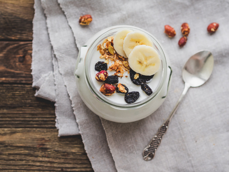 Natural homemade yogurt in a glass jar. Healthy food for breakfast with muesli. Jar with granola and banana slices on linen tablecloth on on wooden table. Standard-Bild