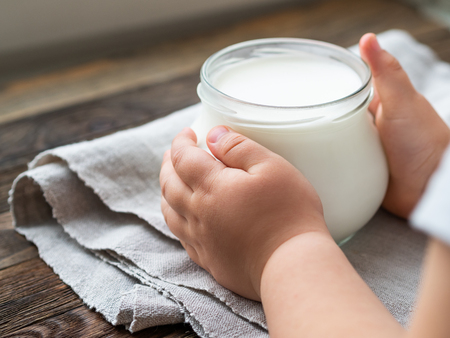 Natural homemade yogurt in a glass jar. Healthy food for breakfast in child's hands. Kid holding jar with sour cream on linen tablecloth on on wooden table.