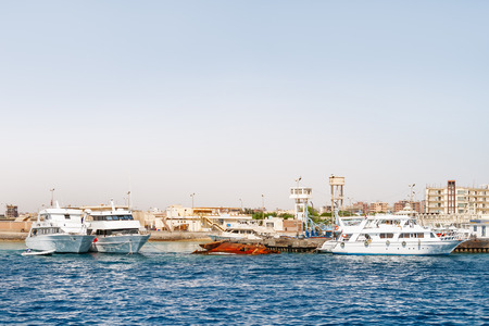 Hurghada coastline with hotels, resort buildings and ships moored to pier. View on seascape from boat. Red sea, Egypt.