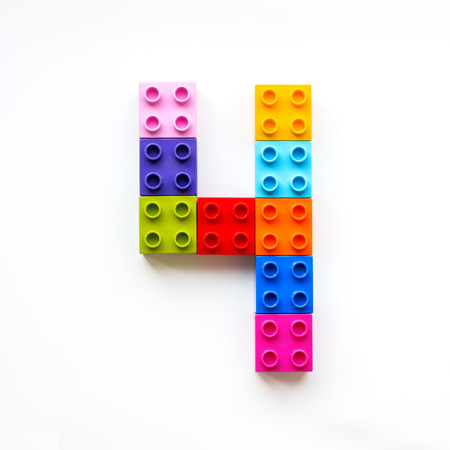 Nummer vier aus bunten Bauklötzen. Spielzeugsteine, die in Ordnung liegen, machen Nummer 4. Bildungsprozess - Lernen von Zahlen mit Kind mit mehrfarbigen Spielzeugdetails. Standard-Bild