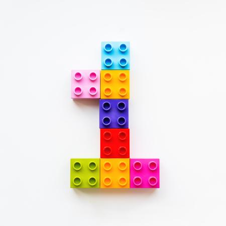 Nummer Eins aus bunten Bauklötzen. Spielzeugsteine, die in Ordnung liegen, machen Nummer 1. Bildungsprozess - Lernen von Zahlen mit Kind mit mehrfarbigen Spielzeugdetails. Standard-Bild