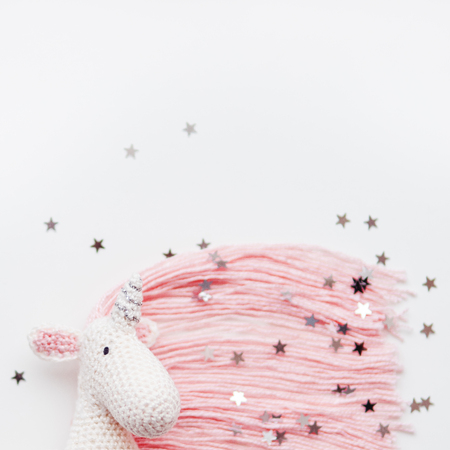 Cute fairy unicorn with a pink mane and a tail made of threads. Crocheted hand made toy on white background with silver stars confetti. Trendy creature, symbol of magic and miracles. Place for text.