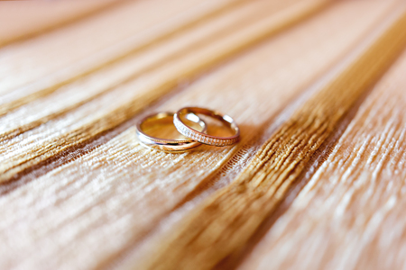 Golden wedding rings with diamonds on beige fabric background. Wedding details, symbol of love and marriage.
