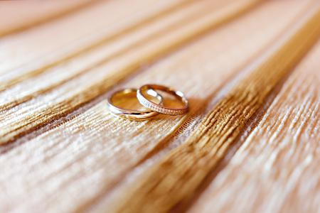 Gouden trouwringen met diamanten op beige stoffenachtergrond. Huwelijksdetails, symbool van liefde en huwelijk.