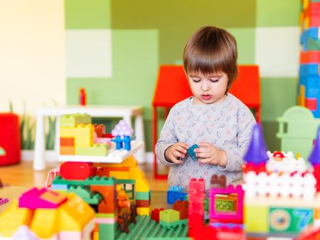 Kleiner Junge, der im Kinderzimmer mit buntem Konstrukteur spielt. Pädagogischer Spielzeugblock in Kleinkindhänden. Kind ist mit Spielzeugziegeln beschäftigt.