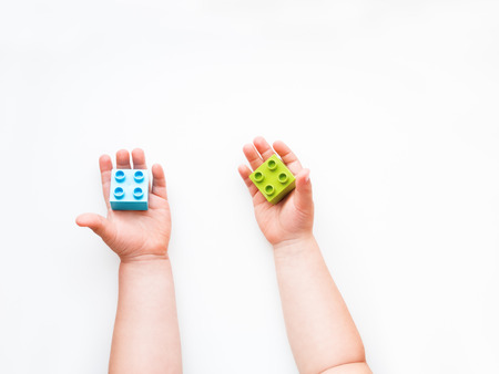 Child is holidng green and blue constructor blocks in fist. Kids hands with bricks toy on white background. Educational toy, flat lay, top view. Banco de Imagens