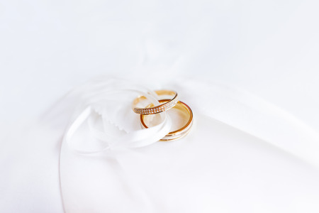 Golden wedding rings with diamonds on white silk fabric. Traditional symbol of love and marriage.