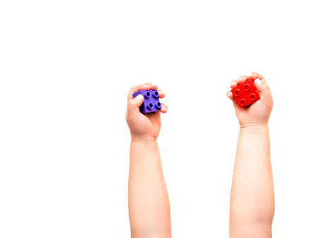 Child is holidng violet and red constructor blocks in fists. Kid's hands with toy on white background. Flat lay, top view.
