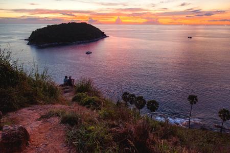 Gorgeous sunset on Kata beach view point. Couple is sitting on hill upon sea. Ko Pu island. Phuket, Thailand.