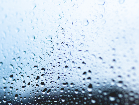Rain drops on glass. Silhouettes of water drops on blue transparent surface. Stock Photo