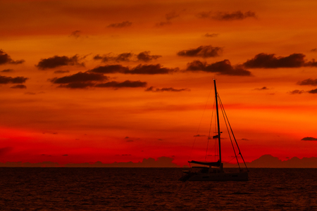 Silhouette of yacht on gorgeous sunset background. Nai Harn beach. Phuket island, Thailand, Indian ocean.