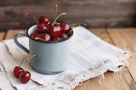 Fresh juicy sweet cherries  in old rusty mug. Rustic wooden background with homespun napkin.
