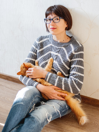 Cute ginger cat dozing on woman knees. Smiling woman in torn jeans stroking her fluffy pet. Cozy home. Imagens