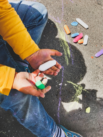 Toddler in jeans draws with crayons on the asphalt in sunny day. Child is holding colored crayons. Kids hands and clothes are covered with colorful chalks. Outdoor leisure activity.