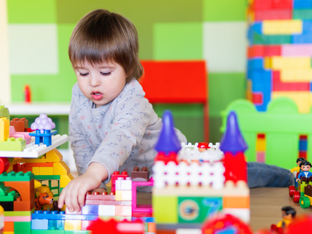 Toddler boy is playing in kidsroom with colorful constructor. Educational toy block in his hands. Kid is busy with toy bricks. Banco de Imagens