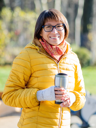 Happy wide smiling women in bright yellow jacketis holding thermos mug. Hot tea or other beverage on cool autumn day.