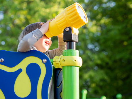 Toddler boy is playing on children playground. Child looking into a toy telescoper. Sunny summer day.