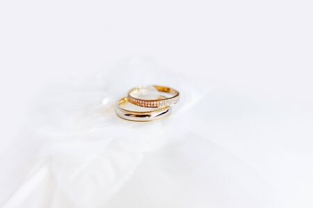 Golden wedding rings with diamonds on silk fabric. Romantic symbol of love and marriage. Traditional jewelry accessory. Imagens