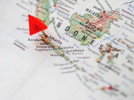 World map with focus on Republic of Indonesia. Red triangle pin on capital city Jakarta. 写真素材