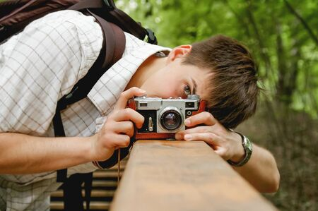 Young man takes a shoot with old fashioned film camera. Handsome man in park. Photographer with retro photo camera. Imagens