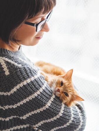Cute ginger cat dozing on woman arms. Smiling woman in grey knitted sweater stroking her fluffy pet. Cozy home.