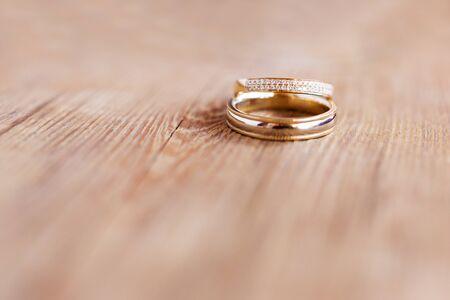 Coppia di fedi nuziali dorate con diamanti su fondo di legno squallido. Simbolo dell'amore, del matrimonio e del quinto anniversario di matrimonio (in legno).
