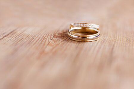 Pair of golden wedding rings with diamonds on shabby wooden background. Symbol of love, marriage and the fifth (wooden) wedding anniversary.