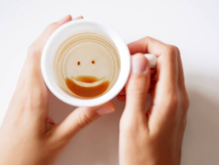 Empty coffee cup with smiling face. Womanholding white mug with coffee grinds. End of coffee break.