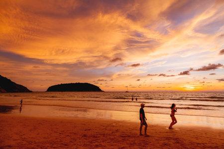 PHUKET, THAILAND - November 18, 2019.  Gorgeous sunset at Nai Harn beach. Tourists on Phuket island, Thailand, Indian ocean.