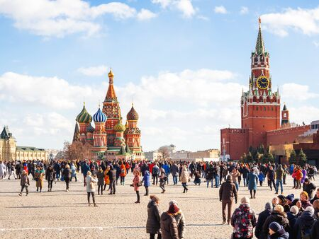 MOSCOW, RUSSIA - March 09, 2019. People walking on Red Square near famous St. Basils Cathedral and Spasskaya tower of Kremlin. Spring celebration - Maslenitsa.