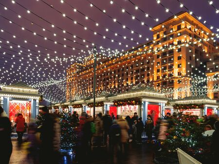 MOSCOW, RUSSIA - January 03, 2018. People walking on Manezhnaya square decorated to New Year and Christmas celebration. Four Seasons hotel. Redakční