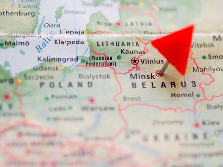 World map with focus on Republic of Belarus with red triangle pin on capital city Minsk.