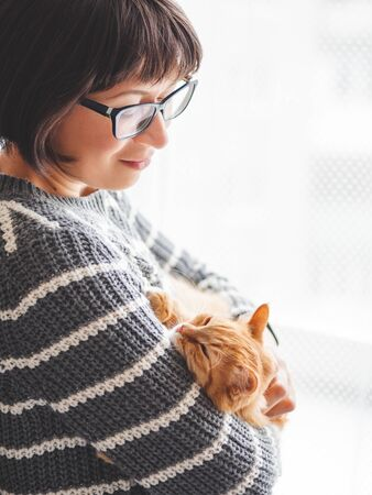 Cute ginger cat dozing on woman hands. Smiling woman in grey knitted sweater stroking her fluffy pet. Cozy home.