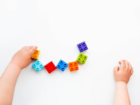Child is playing with colorful constructor blocks. Kids hands with bricks toy on white background. Educational toy, flat lay, top view.
