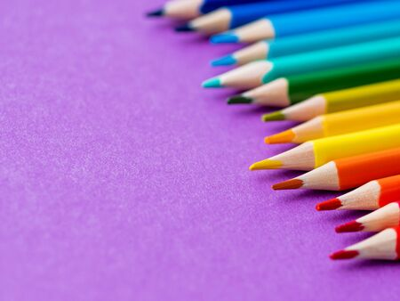 Row of colorful  pencils on lilac background. School supplies on purple paper background. Kids stationery. Back to school magenta backdrop.