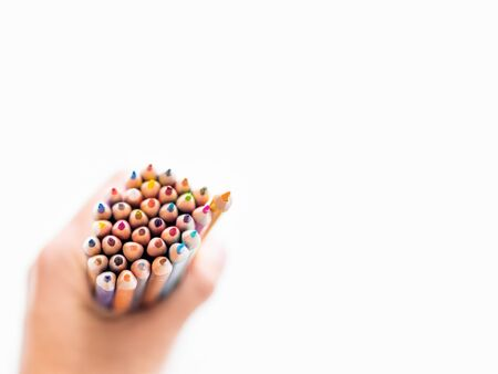 hand with bunch of colorful  pencils on white background. School supplies. Kids stationery with copy space. Back to school backdrop.