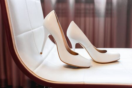 Pair of white hight heeled shoes on beige chair. Bride's fashion accessory for wedding.