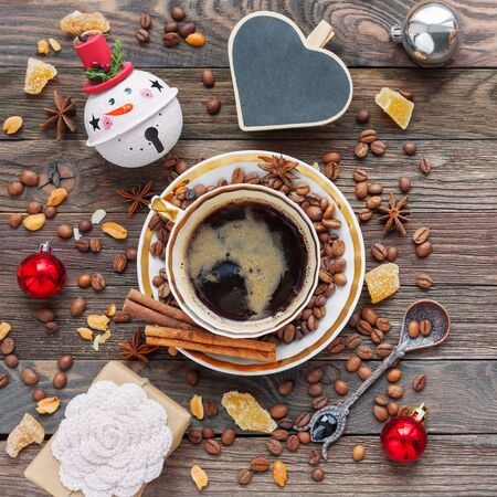 Rustic wooden background with cup of coffee and New Year decorations. Heart shaped chalkboard. Christmas beverage with ginger and anise. Top view, place for text. Stok Fotoğraf