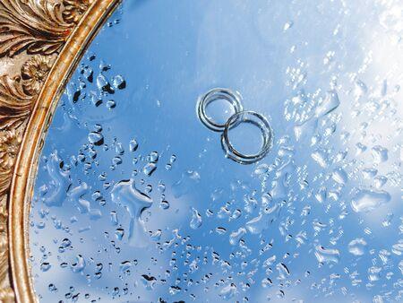Para obrączek ślubnych na mokrej powierzchni lustra z odbiciem błękitnego nieba. Zamknij się zdjęcie z tradycyjną biżuterią panny młodej i pana młodego.