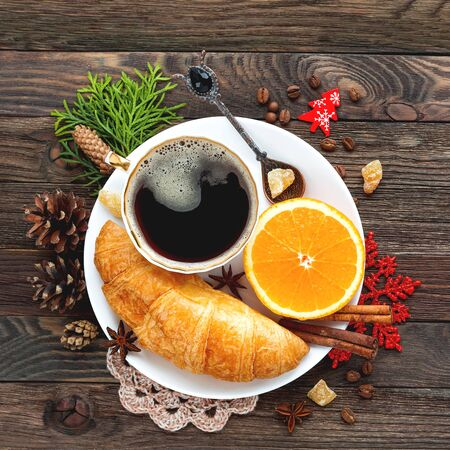 Christmas and New Year 2017 background with continental breakfast - cup of hot coffee with cinnamon, fresh orange and croissant. Decorations - snowflake, crochet napkin, pine cones.