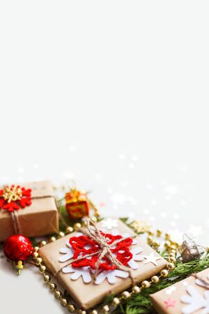Christmas and New Year background with thuja branch, decorations and presents wrapped in craft paper with snowflakes. Copy space. Zdjęcie Seryjne
