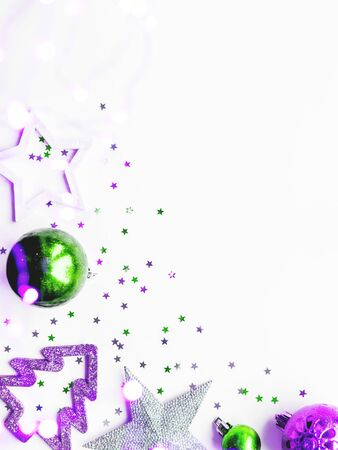 Christmas and New Year background with decorations - green and magenta shiny stars, balls, snowflakes and confetti.